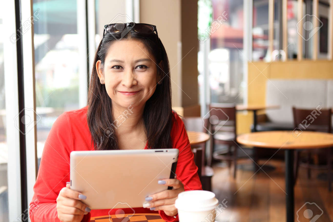 Happy entrepreneur working with a phone and tablet in a coffee shop in the street - 42851585
