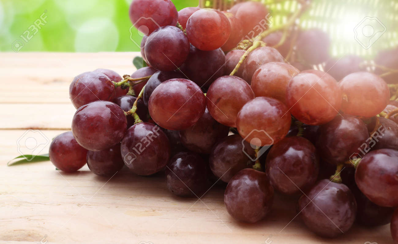 Bunch of red grapes on wooden table - 45278508