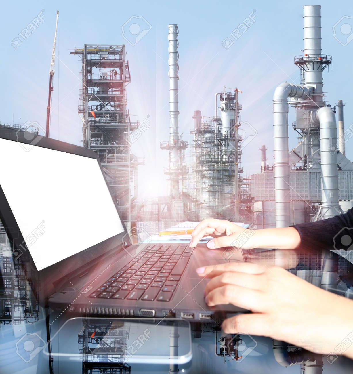 Business woman hand working on laptop computer with oil refinery industry in metallic color style use as metal style of heavy industry background - 47668734