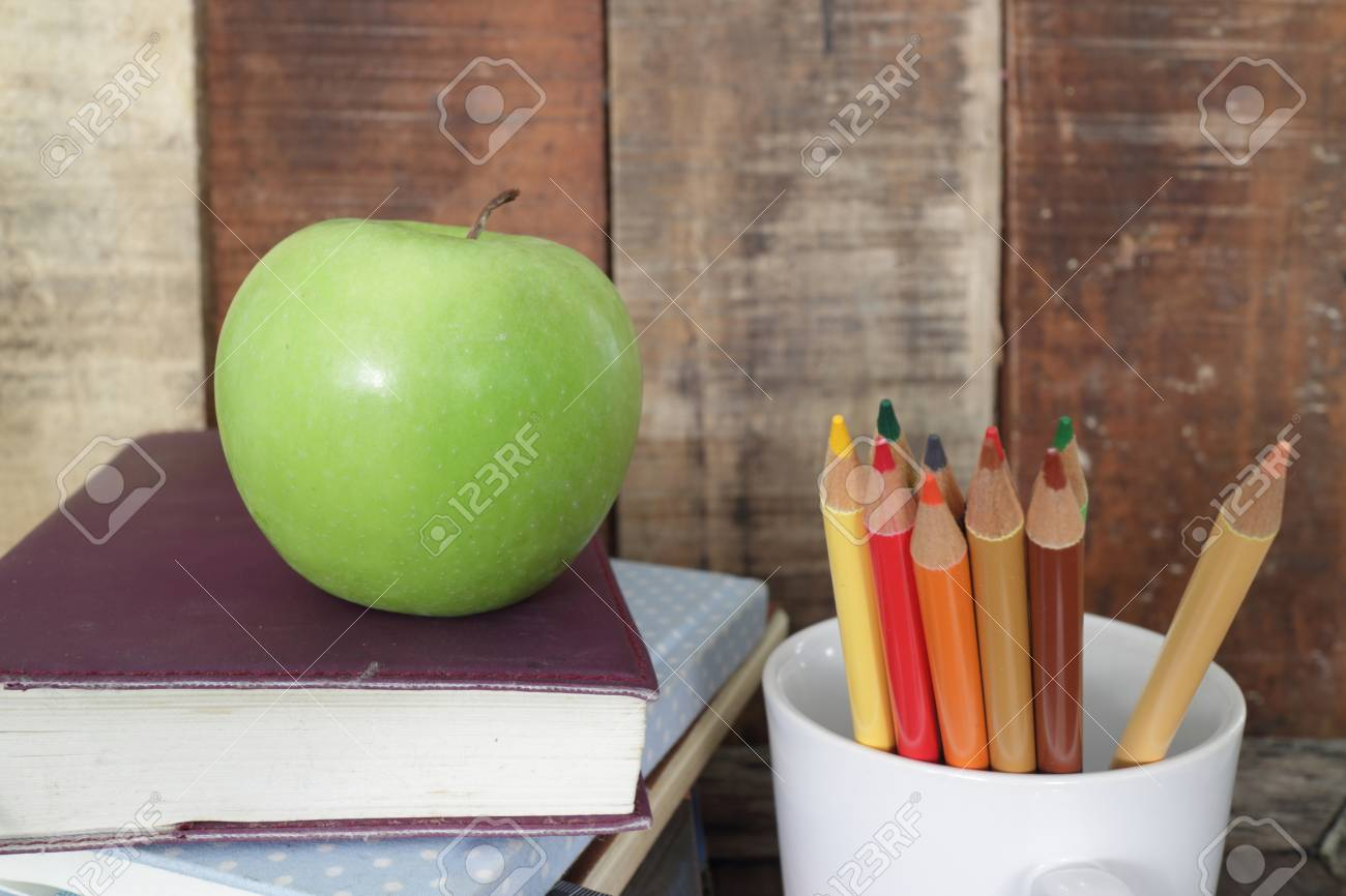 Back To School Lettering With Books Pencils And Apple Over Chalkboard Background Stock Photo