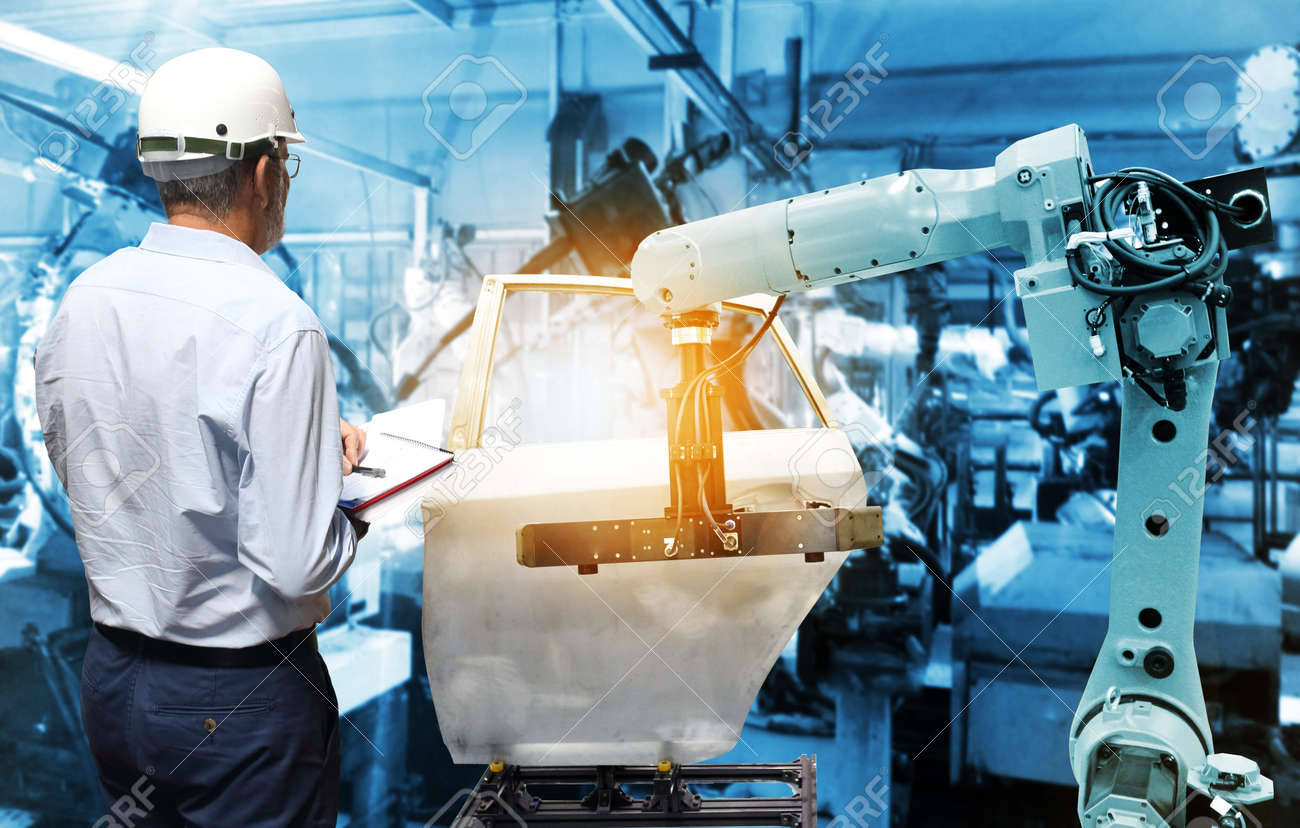 Man hand holding QC check with automate wireless Robot arm in smart factory background. Mixed media of welding robot in the automotive parts industry - 115596091