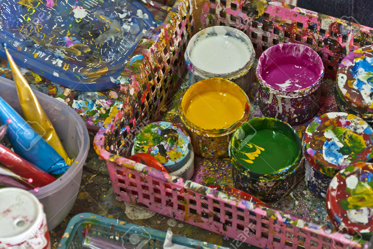 Cans tins with colour oil paints and brushes in press