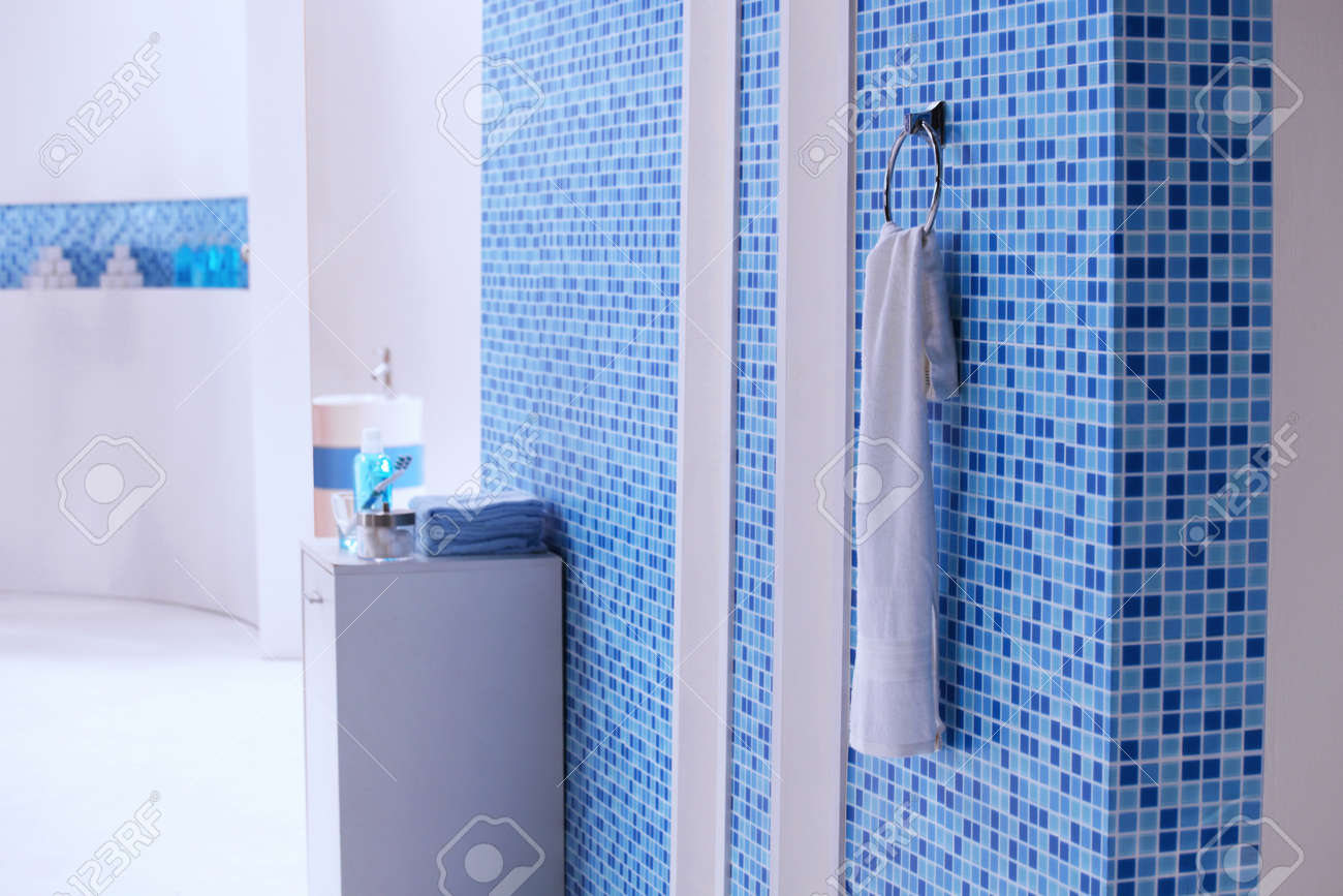 A White Towel Hanging On The Blue Mosaic Tile Wall In The Bathroom