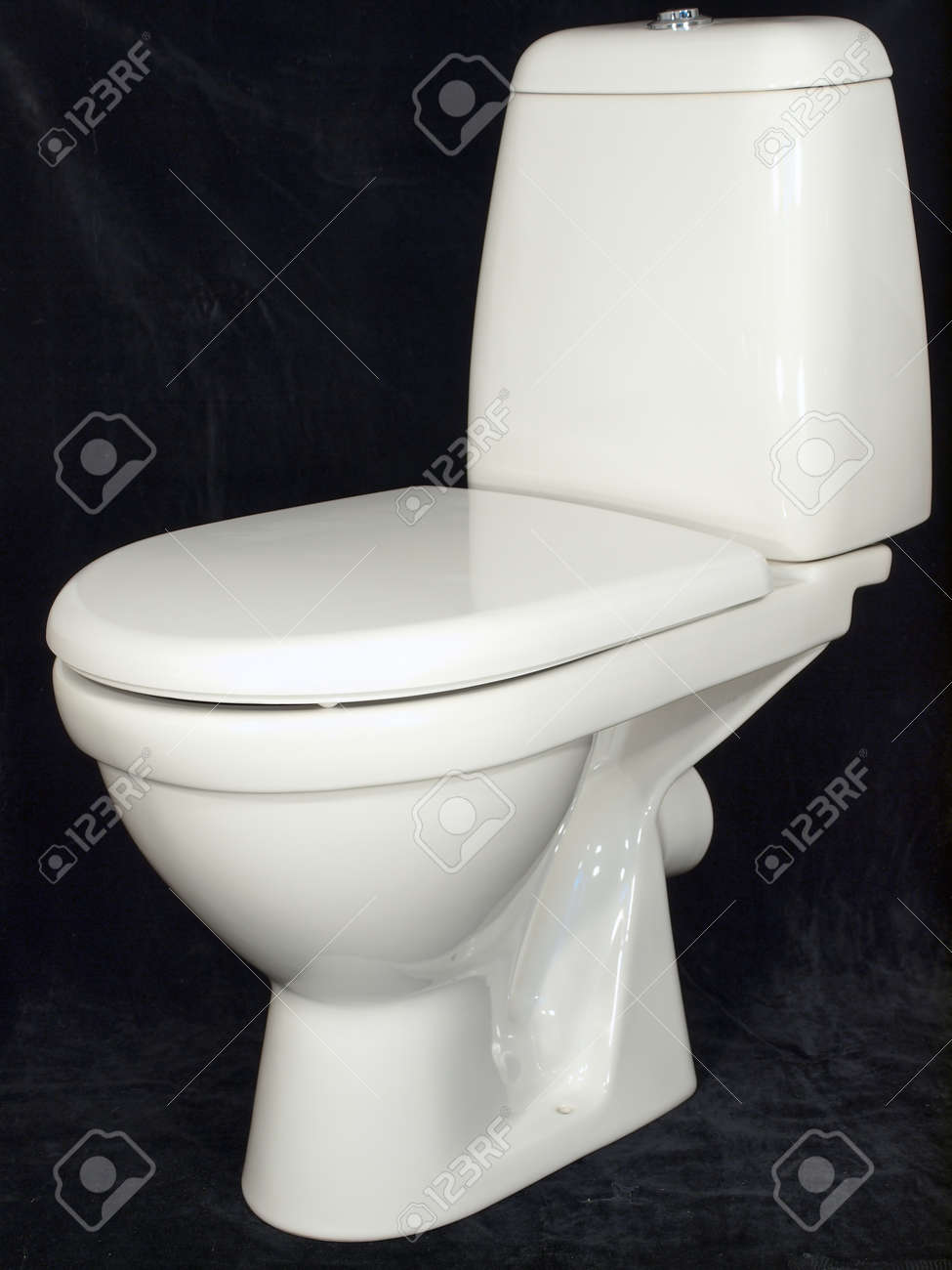 White toilet bowl with the lowered cover on a black background Stock Photo - 9767079