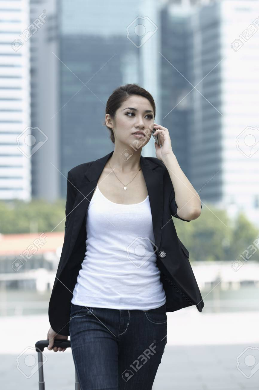 Business woman Walking with a wheeled Suitcase on phone - 10322527