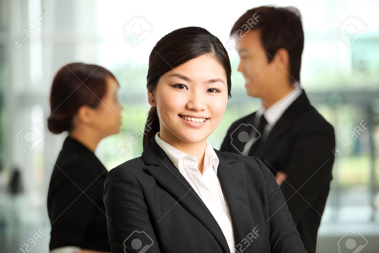 Business woman with colleagues at the back out of focus Stock Photo - 10336541