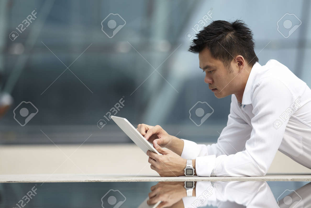 Asian Business man using a  touch pad PC Stock Photo - 10524994