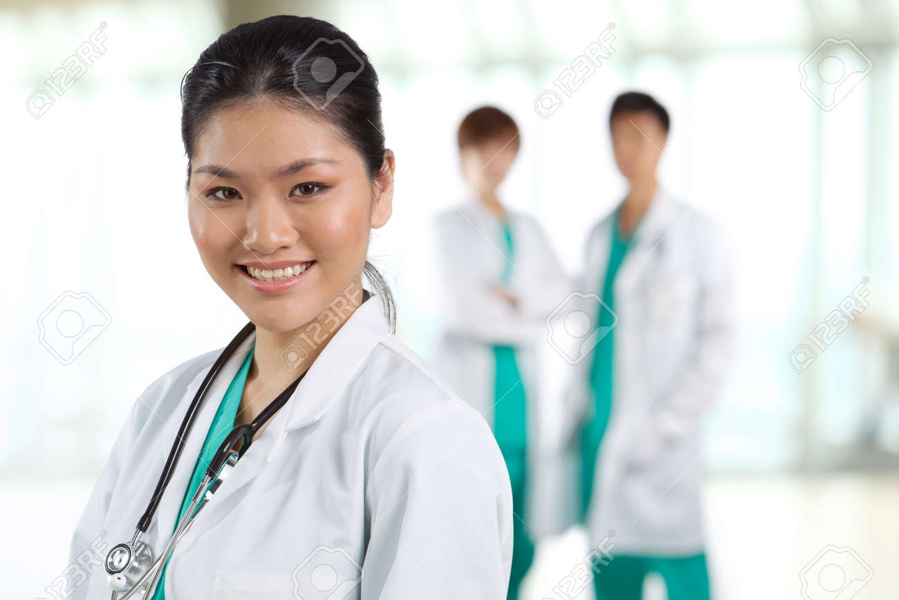 Female doctor with colleague in the background out of focus. Stock Photo - 12596452