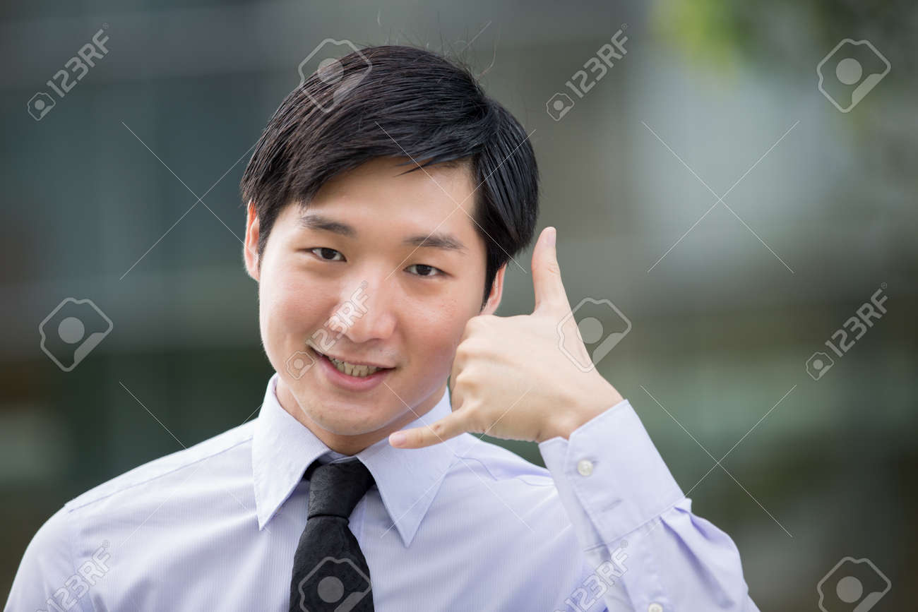 Portrait of an Asian businessman showing the 'call me' symbol with his hands. Stock Photo - 13194305