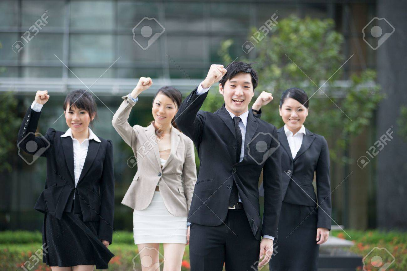 Business man celebrating with his team in the background. Stock Photo - 13194282