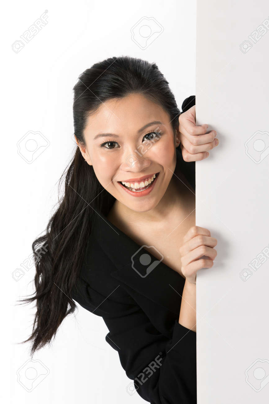 Asian woman peering around from behind a white wall. Stock Photo - 13905384
