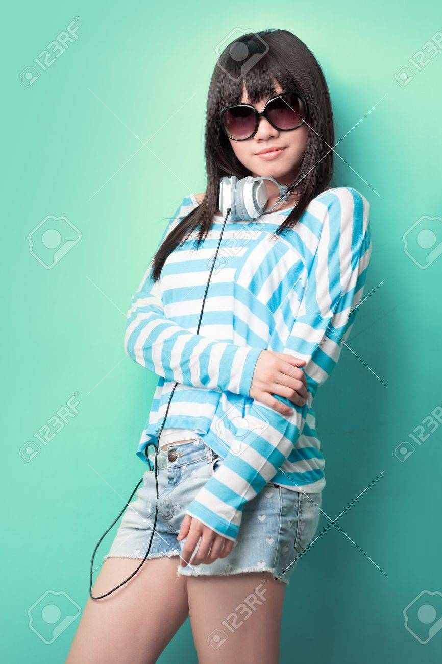 Happy Chinese woman with headphones and sunglasses leaning against a green wall. Stock Photo - 14604029