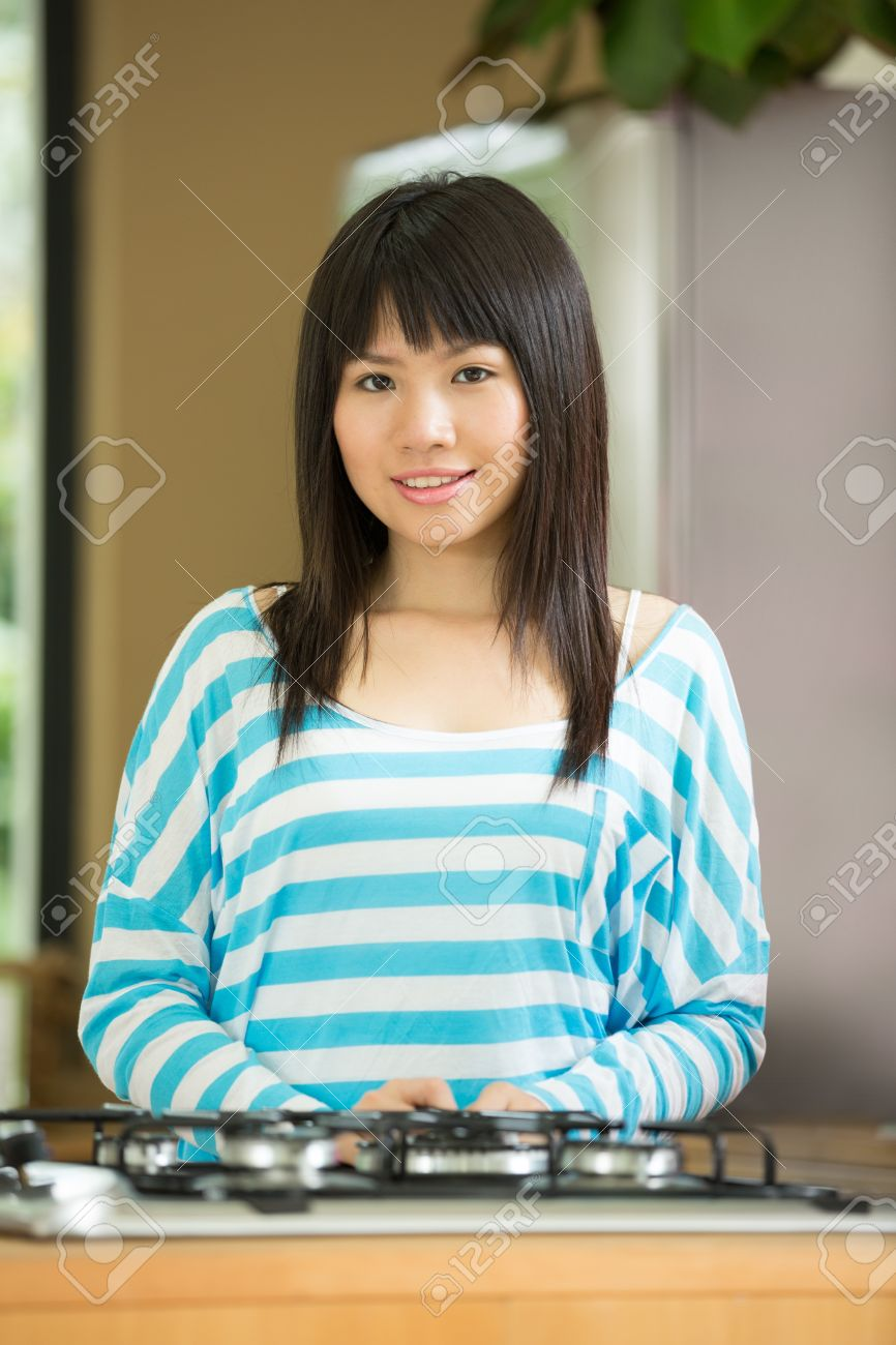 Pretty Chinese Woman Standing In The Kitchen. Stock Photo, Picture ...