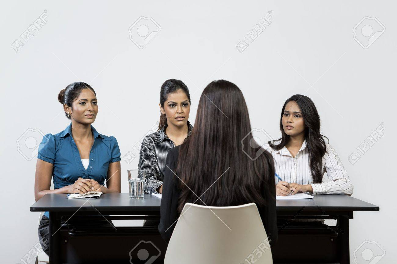 Three Indian colleagues from HR department interview a young female applicant. - 16771686