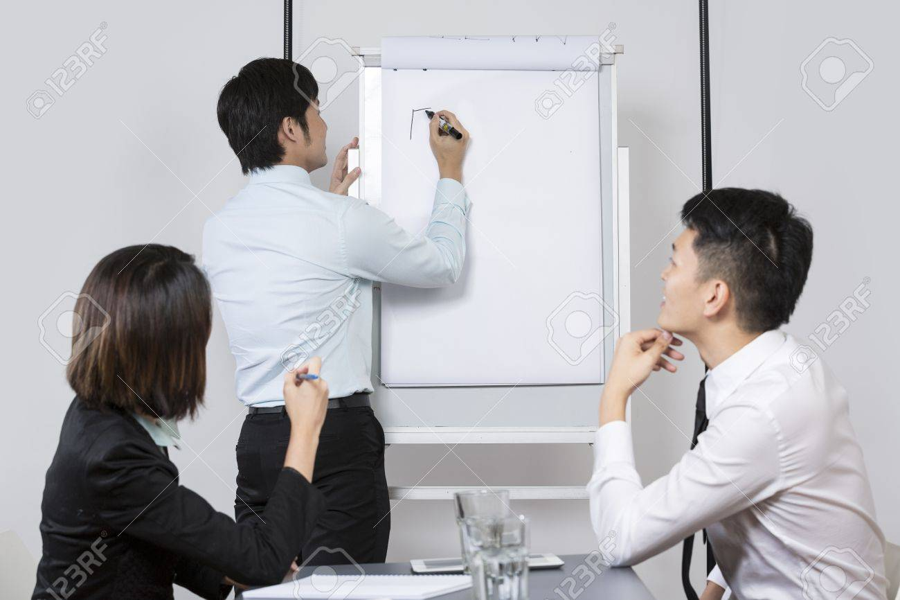 Chinese Business team discussing ideas and writing them on whiteboard. Stock Photo - 16771695