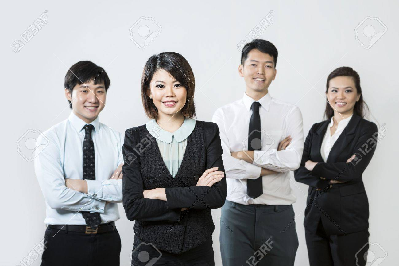Chinese business woman with her team out of focus behind her. Stock Photo - 16771651