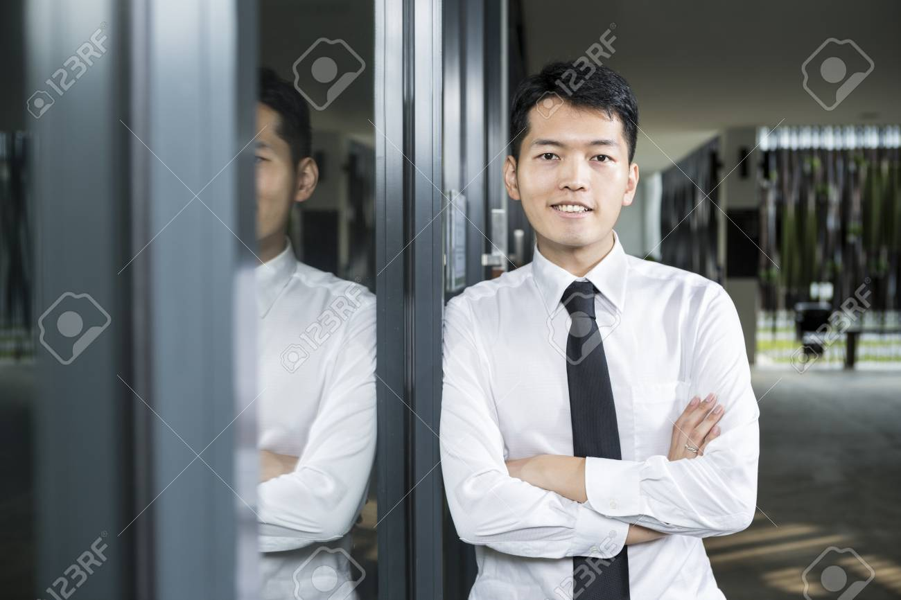 Chinese business man leaning on a window. Stock Photo - 16771778