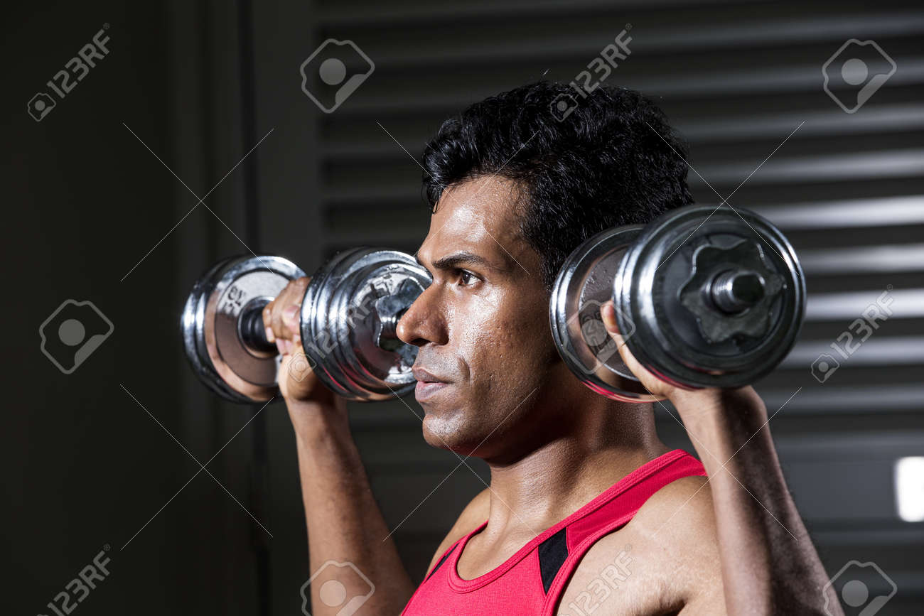 Muscular Asian man exercising with weight training equipment at a sports gym. Stock Photo - 19381702