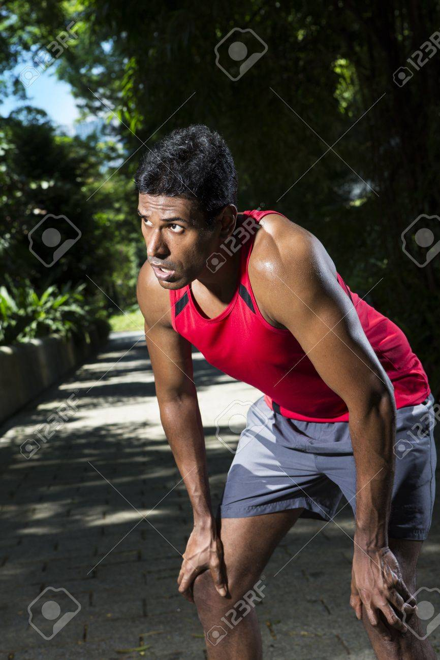 Athletic Indian man having a break from running. Asian Runner jogging in the park. Male fitness concept. Stock Photo - 19590169