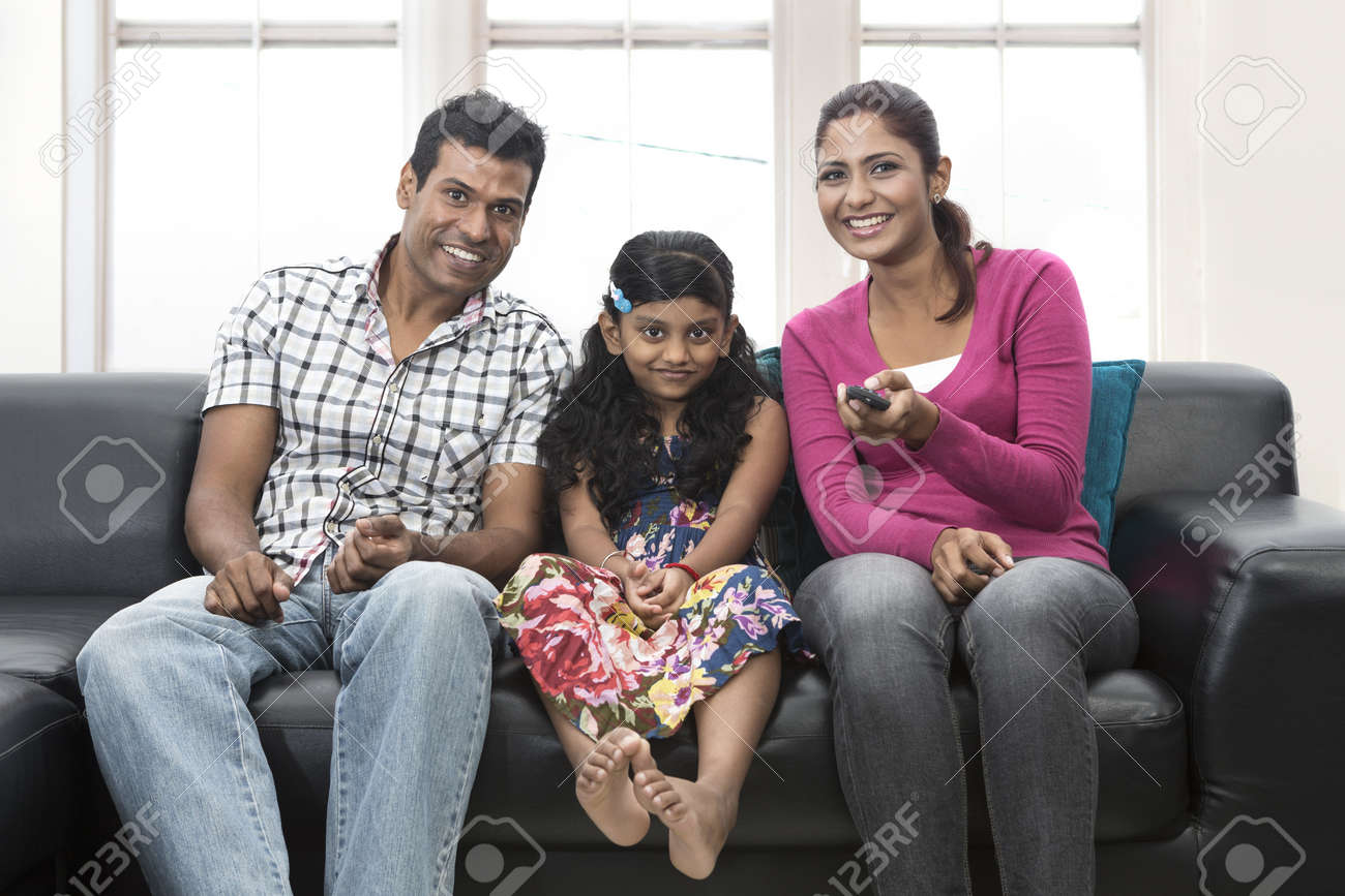 Closeup portrait of mum, dad and child relaxing at home on sofa watching TV. Stock Photo - 19871391