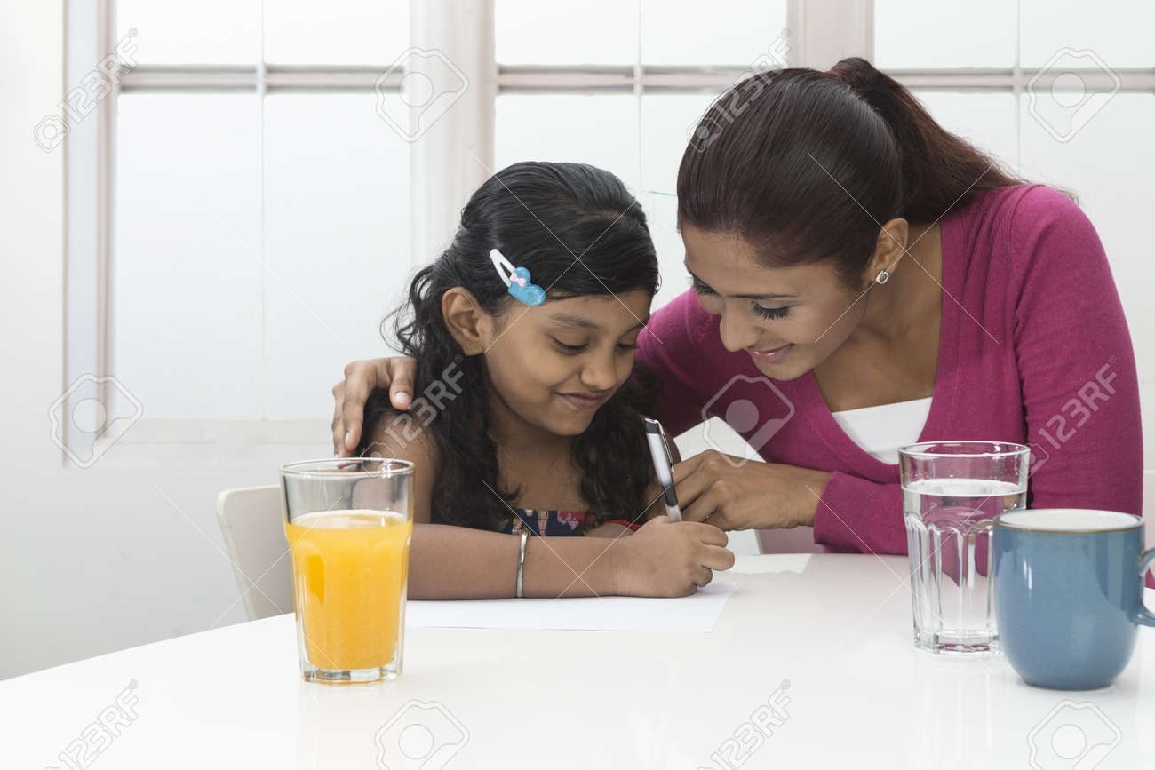 Indian Woman helping young girl with homework at kitchen table. Mother and daughter concept. Stock Photo - 19871510