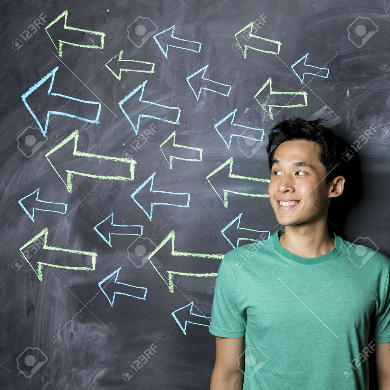 Happy Asian man standing in front of a dark chalkboard with arrow signs drawn pointing. Stock Photo - 21932225
