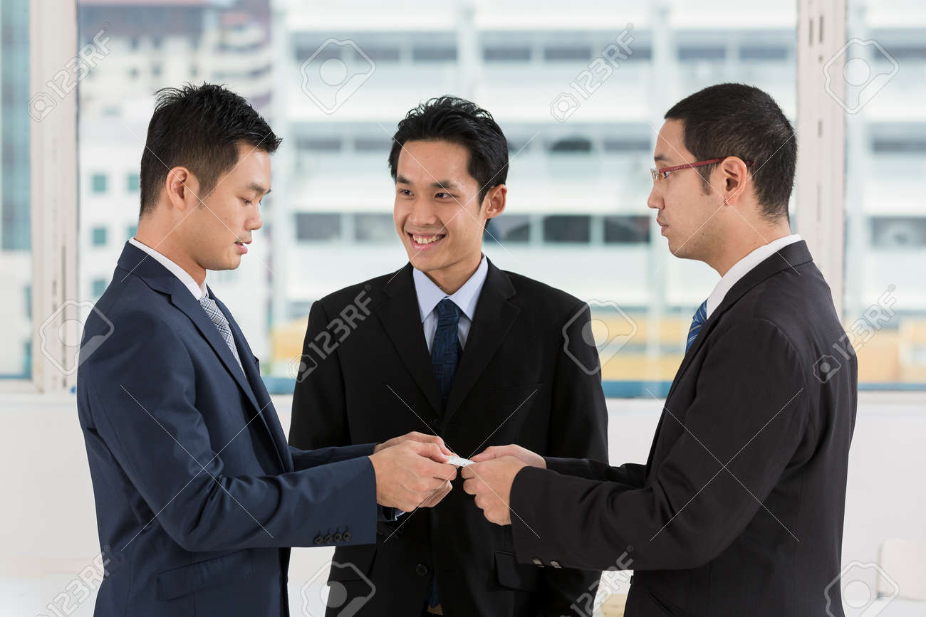Two Business Men Exchanging Business Cards. Caucasian And Asian ...