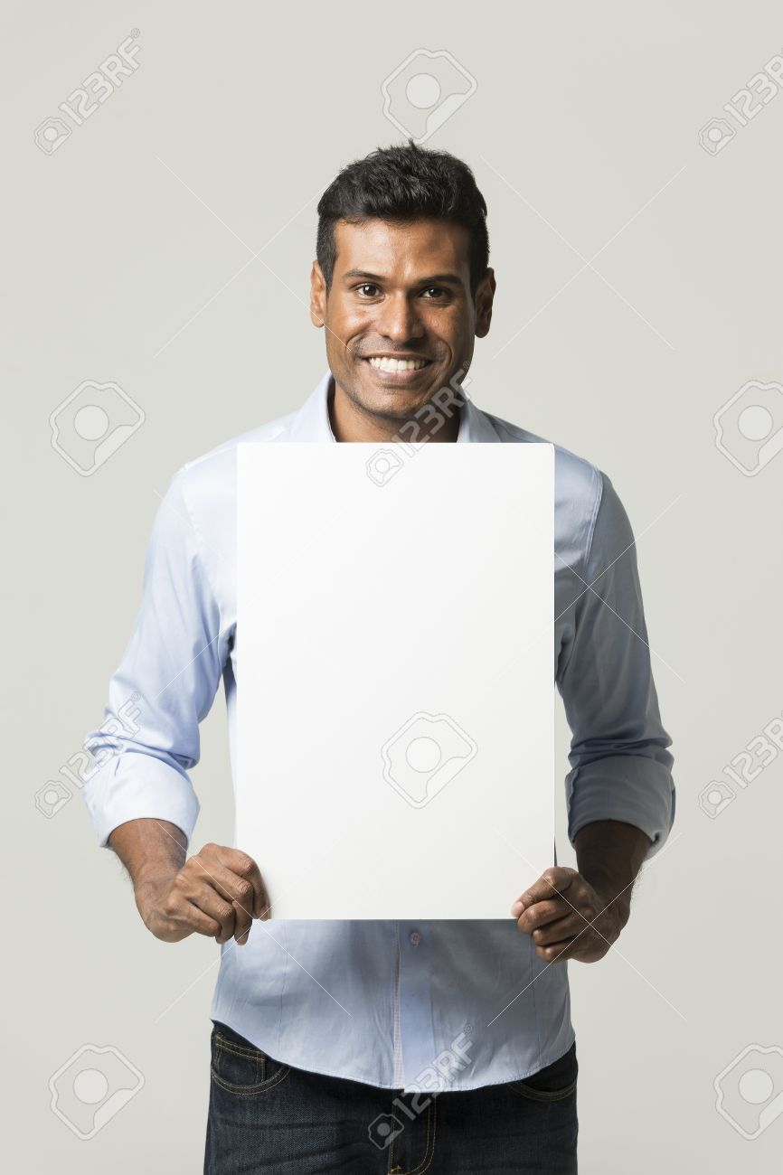Indian man holding up a banner against a grey background. Cardboard placard is blank ready for your message. Stock Photo - 23256902