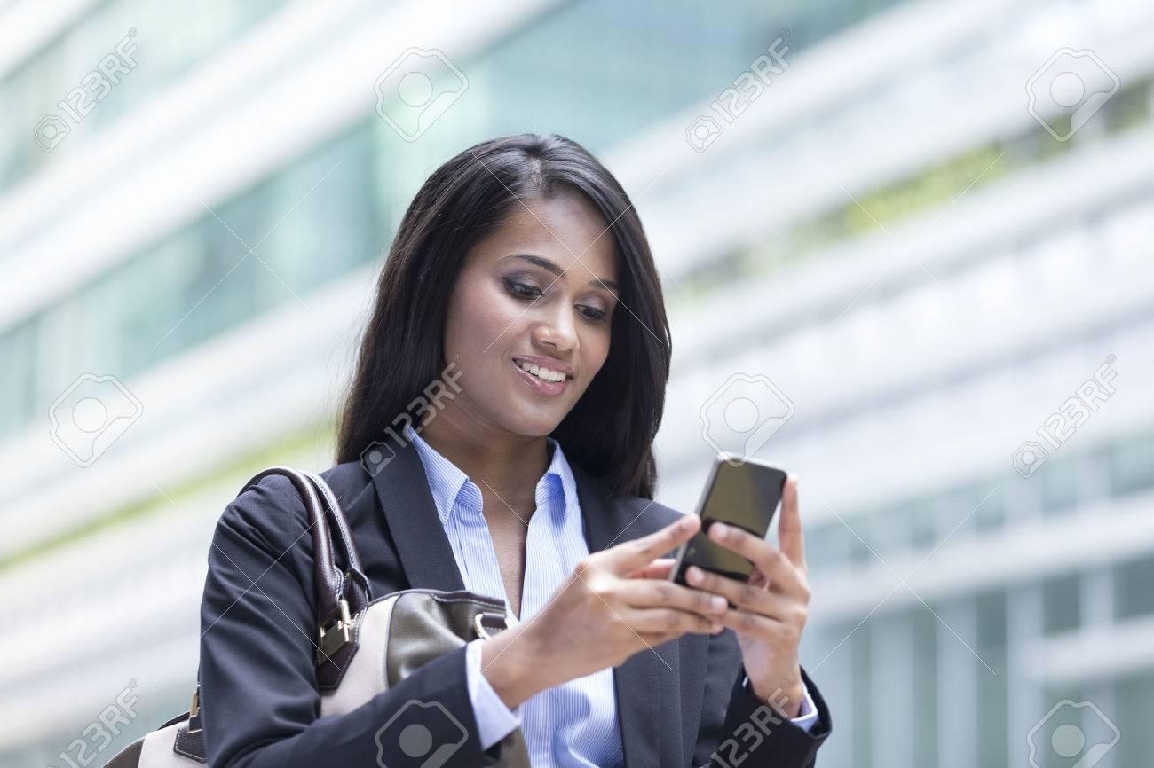 Portrait d'une femme d'affaires indien debout à l'extérieur en utilisant le téléphone mobile pour envoyer un message Banque d'images - 28028293