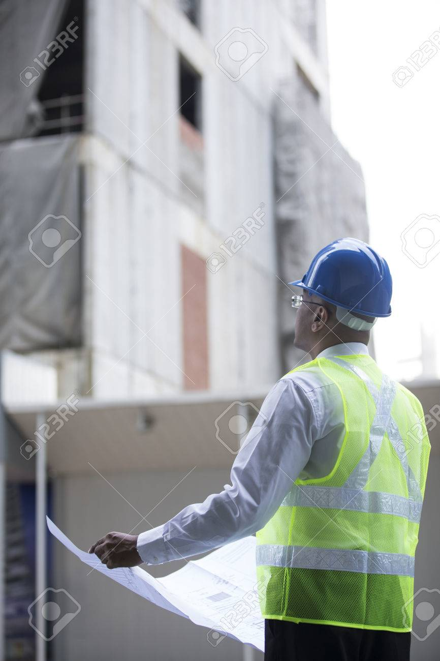 Indian Architect or engineer at work on a building site. Checking plans against the construction work. Stock Photo - 28028457