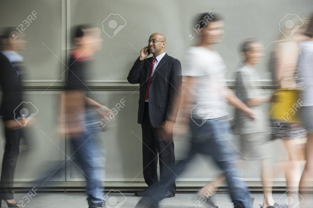 Indian Business man using a Cell Phone with People walking past in a rush. Stock Photo - 28028525