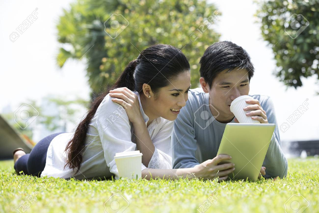 Young Chinese couple using tablet PC in urban city park. Stock Photo - 28190249