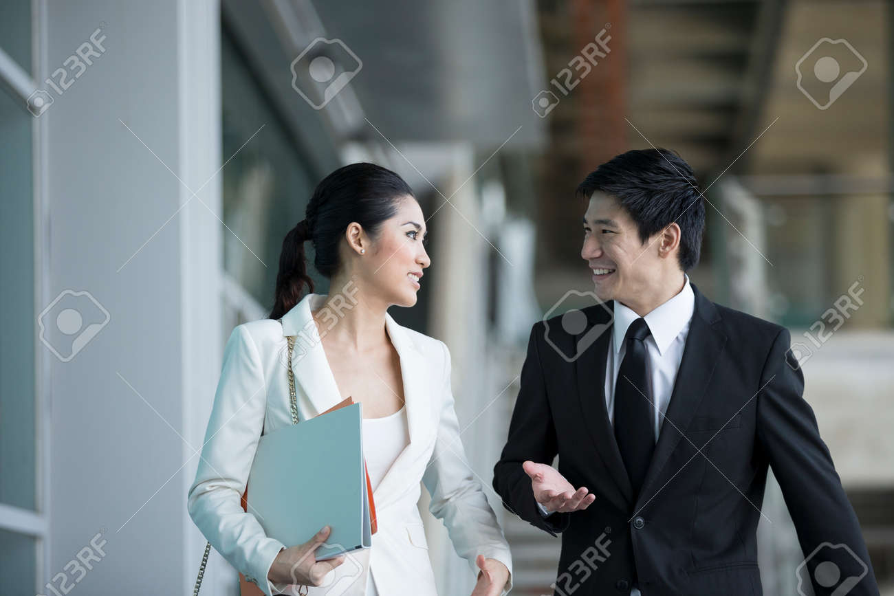 Happy Chinese Business colleagues walking outside office & talking to each other. Stock Photo - 28190379
