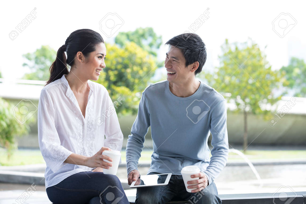 Portrait of an attractive young Chinese couple relaxing together at park. Stock Photo - 28190450