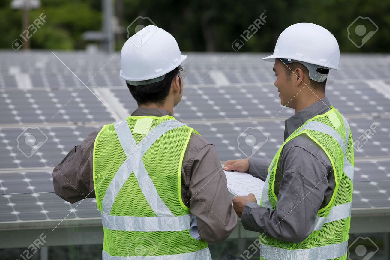 looking over the shoulder of two Chinese maintenance engineers discussing solar panels. Banque d'images - 28193205