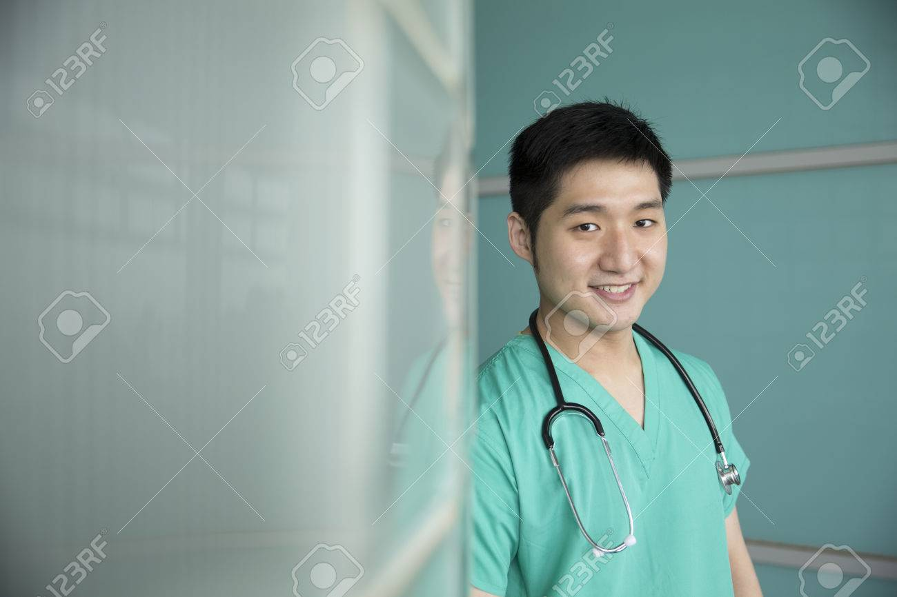 Portrait of a confident Chinese surgeon or doctor wearing green scrubs.  Medical people portrait.