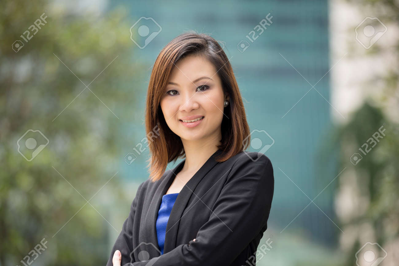 Portrait of a beautiful Chinese businesswoman in smart business suit. Asian business woman standing outside in modern city. Stock Photo - 28540848