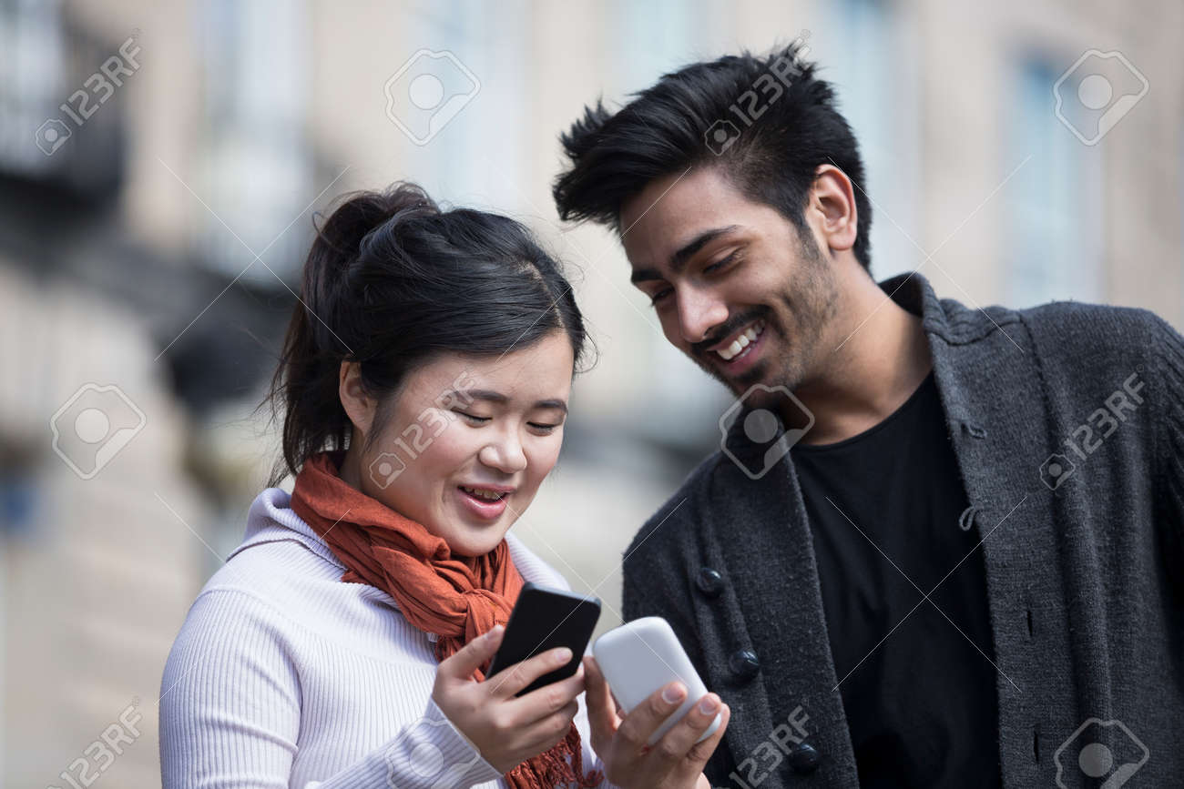 Happy Asian friends using mobile phone outside in street. Young urban couple 'hanging out' in the city using tech. Stock Photo - 28608224