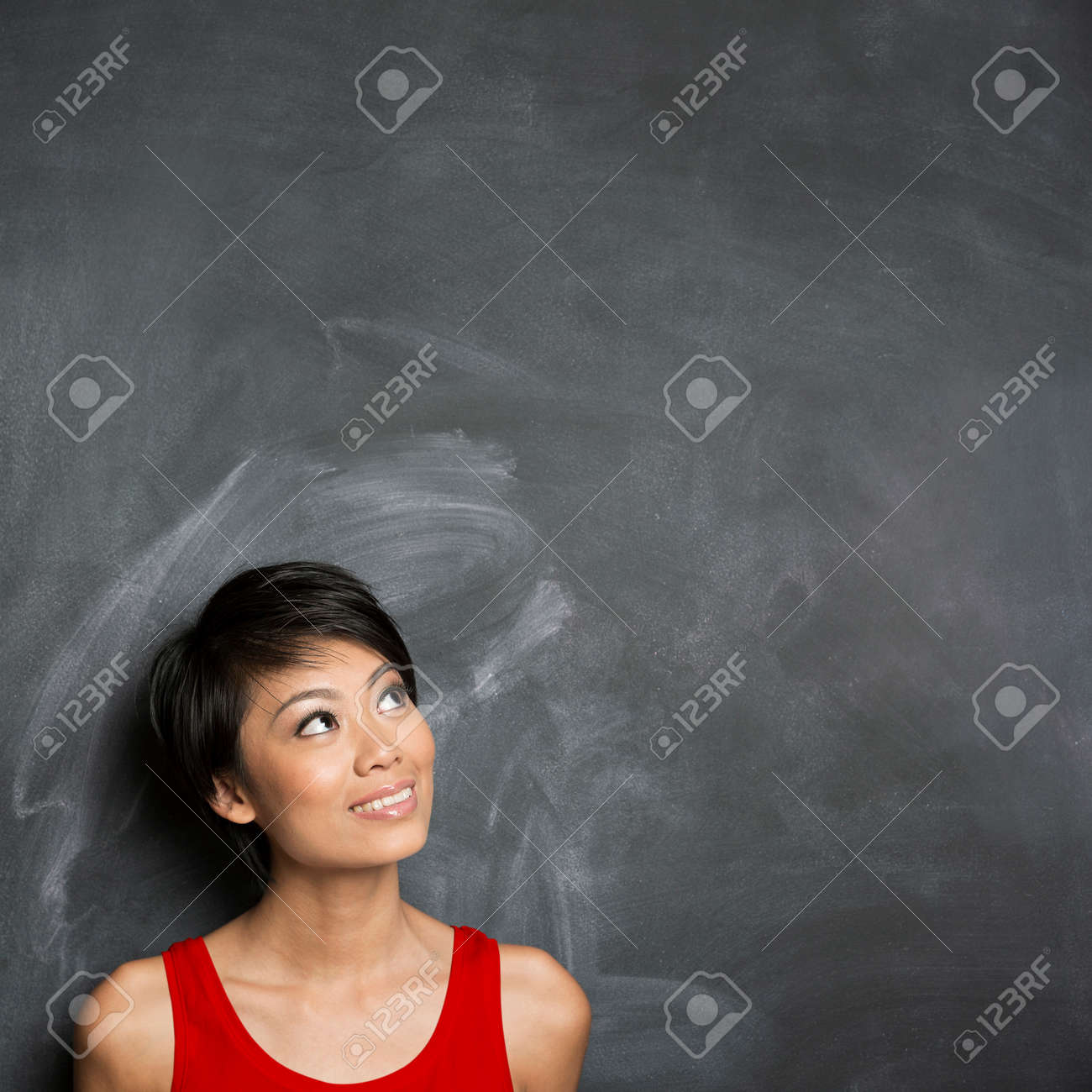 Happy Chinese woman standing in front of a dark chalkboard. The chalk board is blank waiting for a message. Stock Photo - 29578908