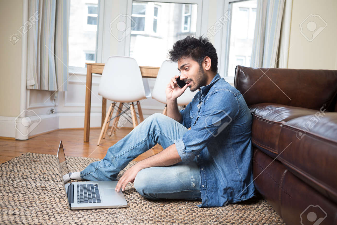 Asian Man using a laptop and talking on phone at home in the lounge. Stock Photo - 30481756