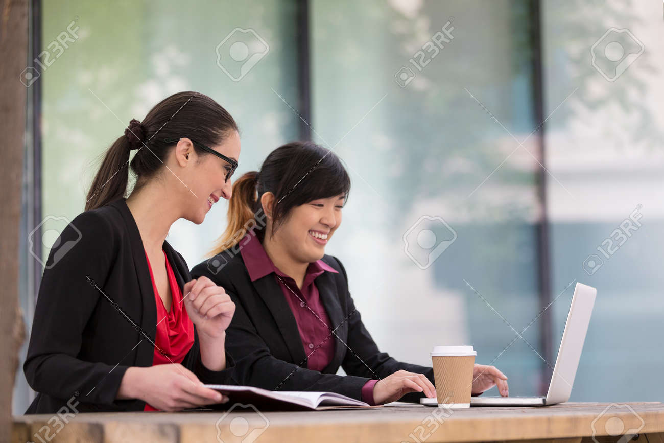 Two female Business women working on a laptop computer. Caucasian and Asian business colleagues at work. Stock Photo - 30613420