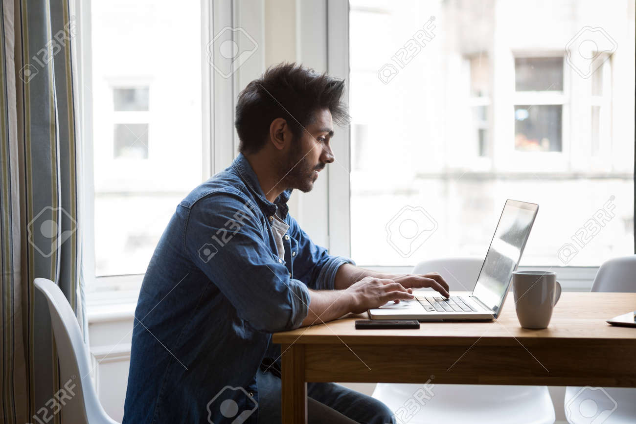 Portrait of an Indian man sitting at a table at home working on a laptop computer. Side View. Stock Photo - 31164412