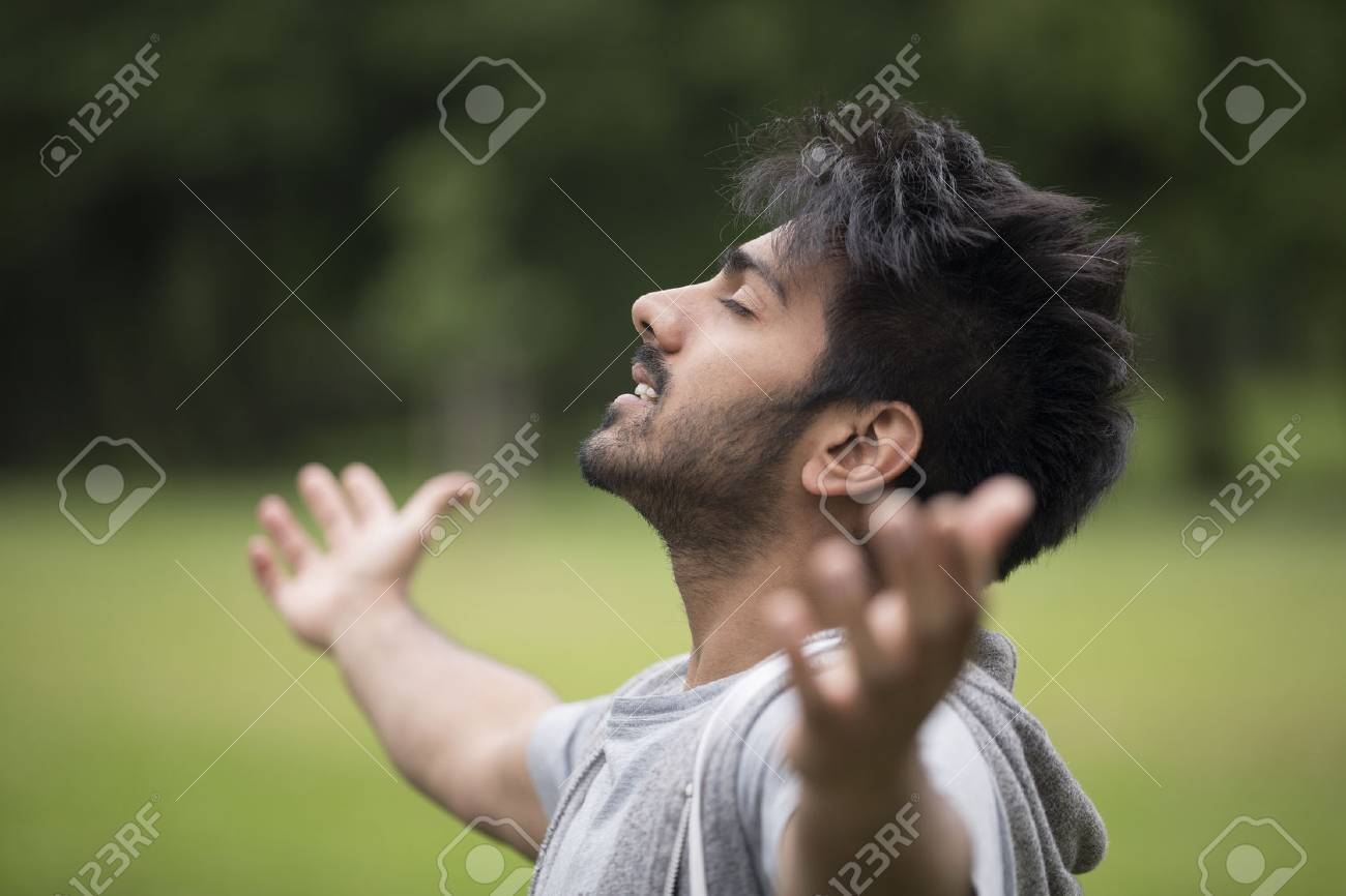 Asian man standing with arms raised outdoors. Concept about freedom, faith and celebration. Stock Photo - 31164674