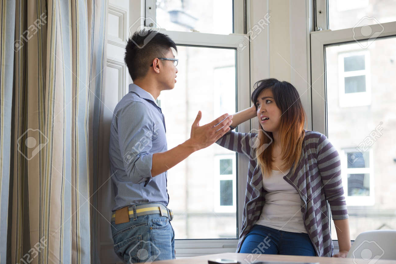 Young Chinese couple arguing in their living room. Stock Photo - 32983220