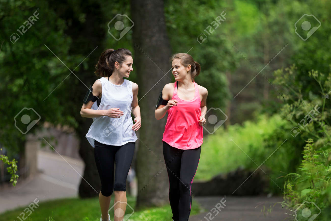 Two athletic women running outdoors Stock Photo - 43009633