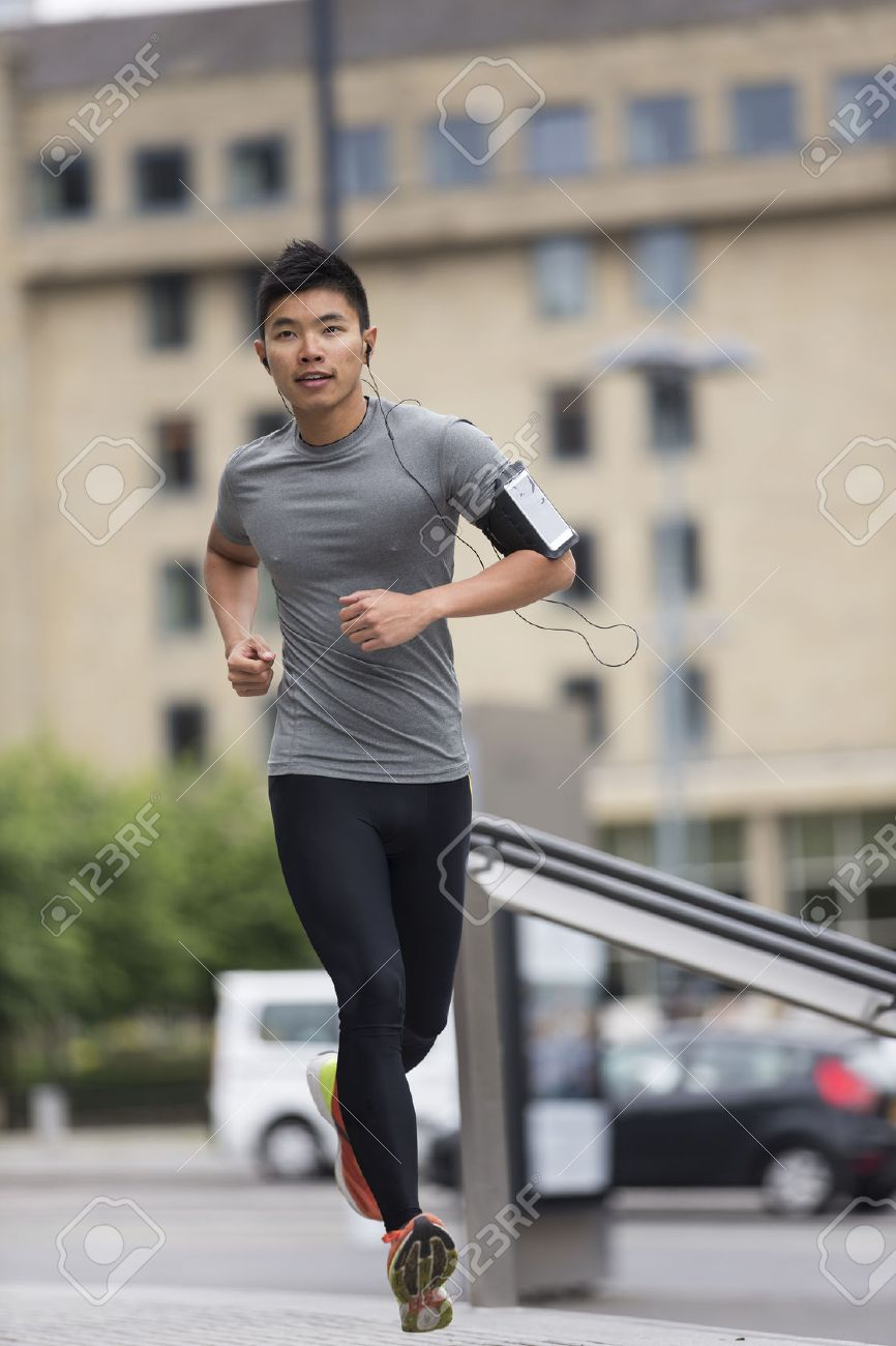 Athlete Chinese man running outdoors in urban city. Asian running man, listening to music on smart phone while running. Sporty Male fitness concept. Stock Photo - 43884277