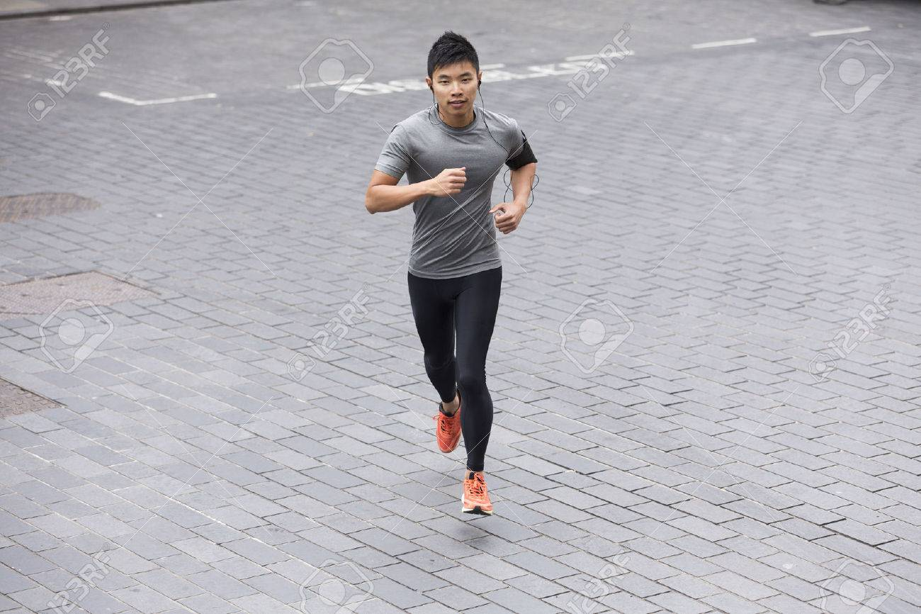 High angle view of a Sporty fit Asian man jogging on street listening to music on smart phone. Male fitness concept. Stock Photo - 43884291