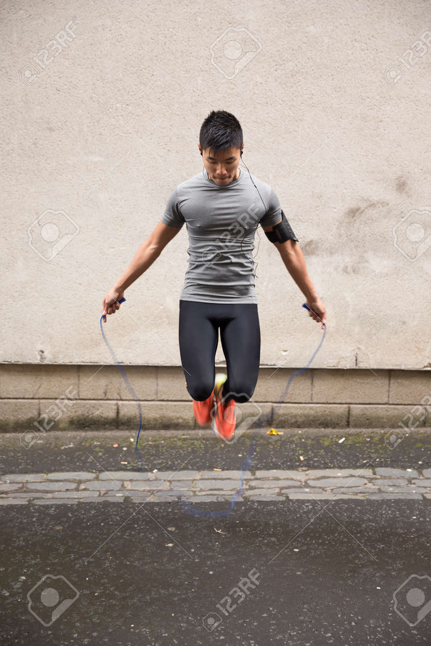 Portrait of athletic Chinese man using a skipping rope in a city street. Stock Photo - 43884292