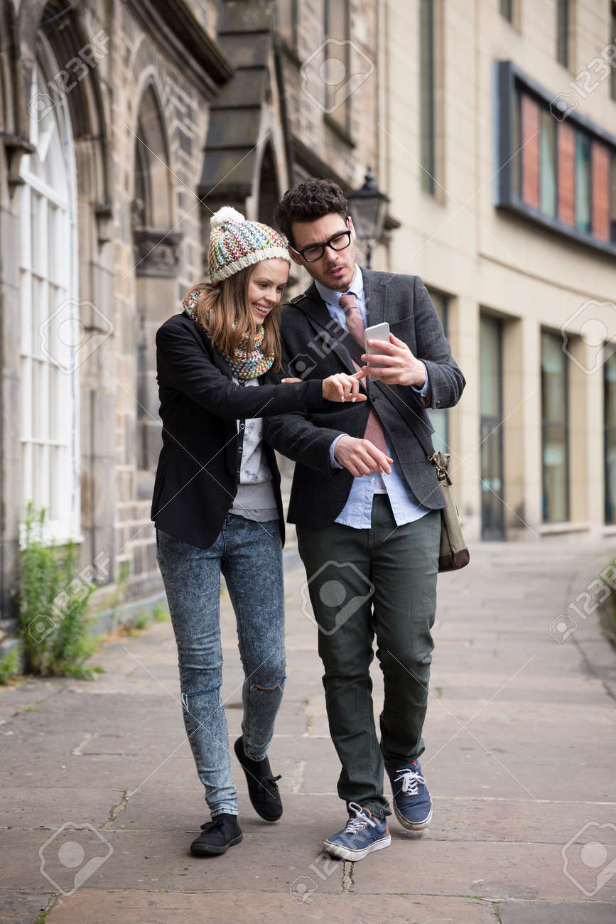 Happy Caucasian couple walking down the street using a Smart Phone. Young man and woman walking together. Stock Photo - 44444245