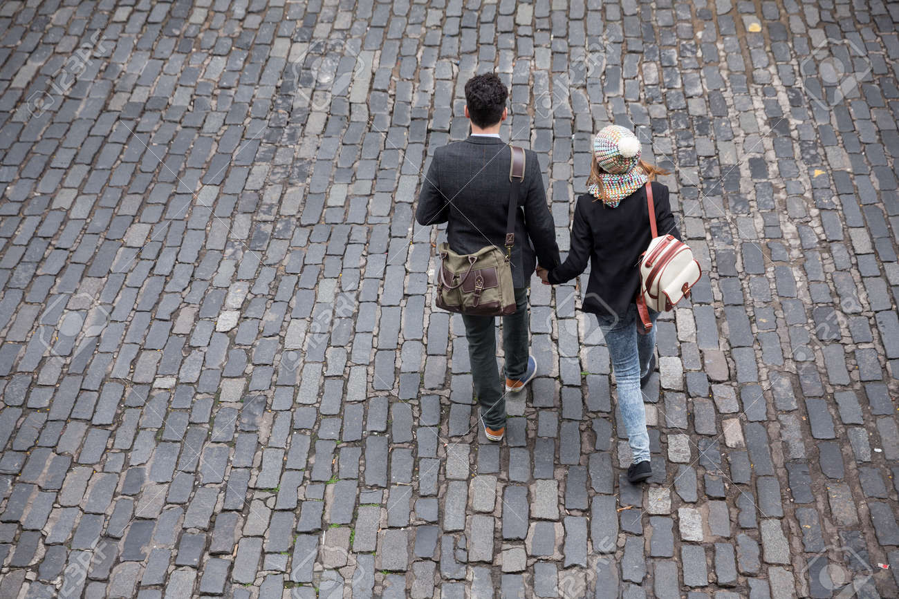 High angle view of a couple walking down the street using a Smart Phone. Young man and woman walking together. Stock Photo - 44444281